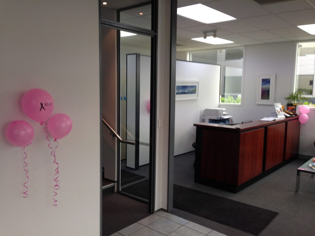 Photo of the head office reception featuring pink breast cancer balloons
